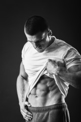 A man shows his abdominal muscles