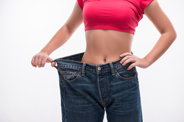 Slim waist of young woman in big jeans showing successful weight