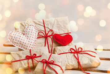Gift boxes and hearts on white wooden background