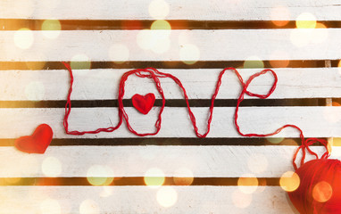 Love word formed with red knitting yarn on wooden background