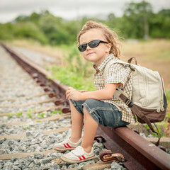 little boy with backpack sitting on the railway