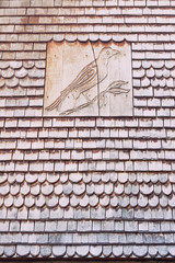 Roof with wooden tiles and the image of a bird in Troyes.
