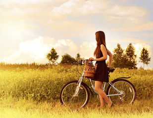 beautiful girl riding bicycle in a grass field