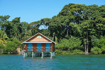 Bungalow over the sea with tropical vegetation