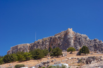 Medieval fortifications on top of the rock in Lindos .