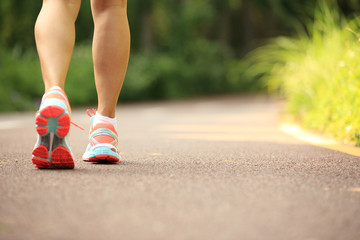 young fitness woman legs running at forest trail
