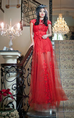 The beautiful girl in a long red dress posing in a vintage scene