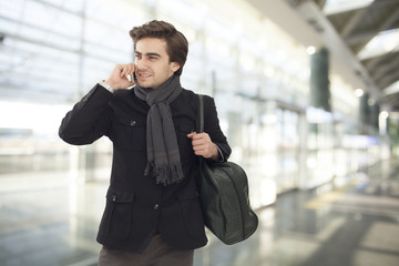 Young businessman talking on mobile phone  in airport