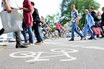 Mixed crowd of pedestrians crossing street and bike lane