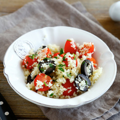 couscous salad with vegetables and olives in white plate