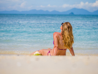 Woman on the beach with coconut drink