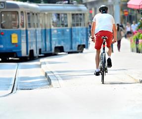 Bike commuter and tram in sunlit city