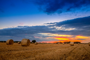 End of day over field with hay bale Wall mural
