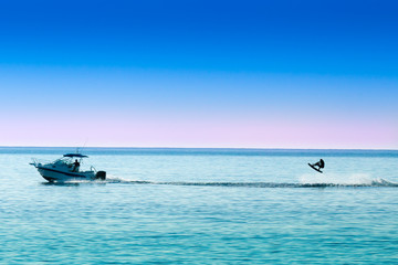 silhouette of motor boat and wakeboarder jumping crazy trick Wall mural