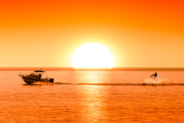 silhouette of boat and wakeboarder at sunset Wall mural
