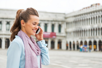 Portrait of happy young woman talking cell phone in venice
