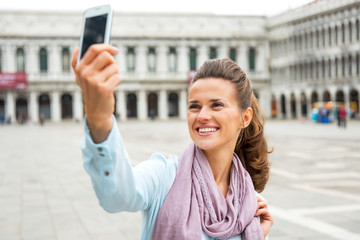 Woman taking self photo with cell phone in venice, italy