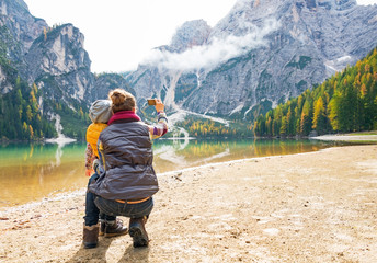 Mother and baby taking photo while on lake braies in italy
