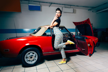 Pretty young woman posing in vintage garage