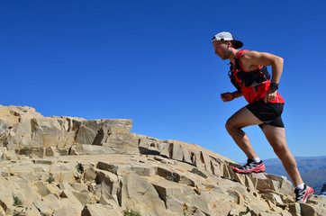 Man running on a high mountain trail