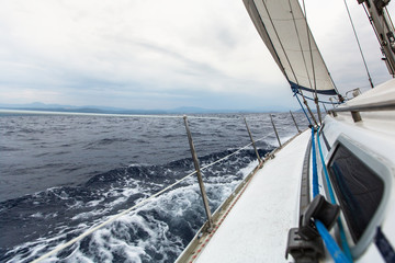 Sailing yacht on the race in a stormy sea.