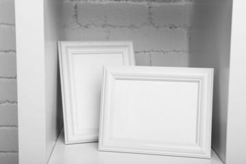 Photo frames on shelf on brick wall background
