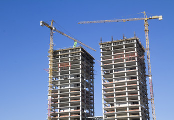 Construction site with cranes on blue sky
