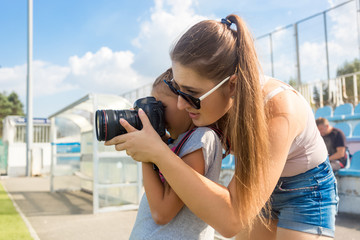 woman teaching little girl to photograph using professional came