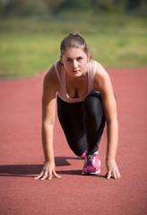 brunette woman standing on start line and ready to run