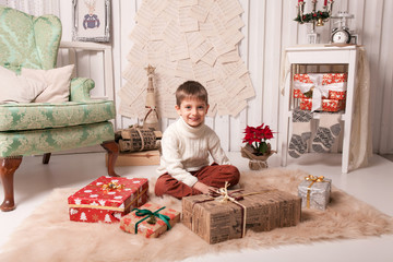 Little boy holding present box in Christmas interior