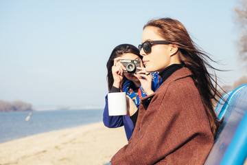 Two girls take pictures on the beach with an old camera