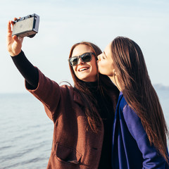 Two girlfriends doing selfie on the beach
