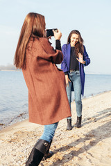 girl taking pictures her cheerful girlfriend on the beach