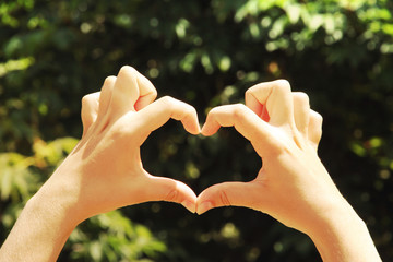 Young woman's hands making heart shape frame