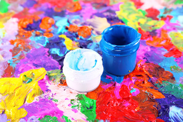 Cans of paint on colorful painted background