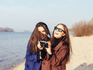 girls taking pictures on the beach in front of the sea