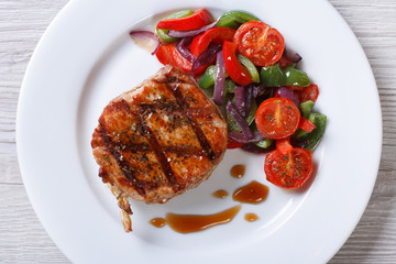 pork steak with vegetables and sauce top view horizontal