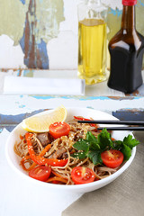 Chinese noodles with vegetables and roasted meat in bowl
