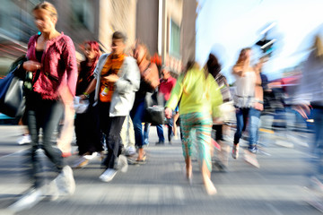 Zoom and motion blurred crowd crossing street