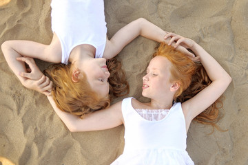 portrait of two sisters walking on the beach