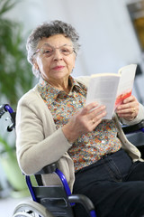 Disabled elderly woman in wheelchair reading book