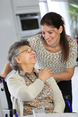 Portrait of elderly woman in wheelchair with home carer