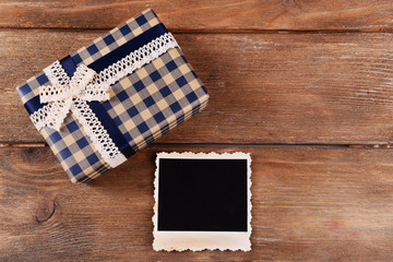 Blank photo frame and present box on wooden table background