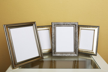 Vintage photo frames on coffee table on wallpaper background
