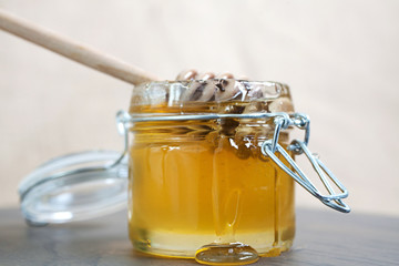 Honey drip with jar isolated on jute background.