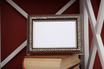 Photo frame with books on shelf, on color wall background