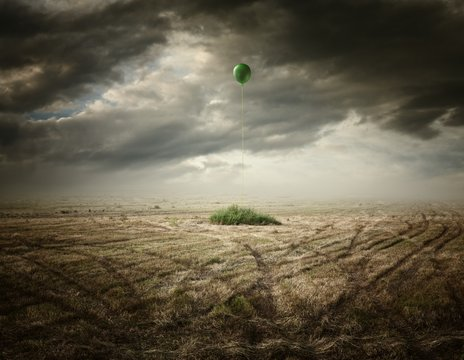 Surreal artistic illustration with a balloon on dry grass