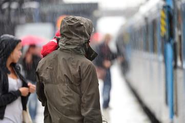 Man in raincoat in heavy rain on train station platform