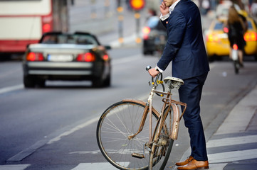 Fototapete - Man in perfect suit and old bike, typical Stockholm Scene
