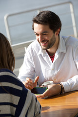 Young man smiling and showing woman mobile phone